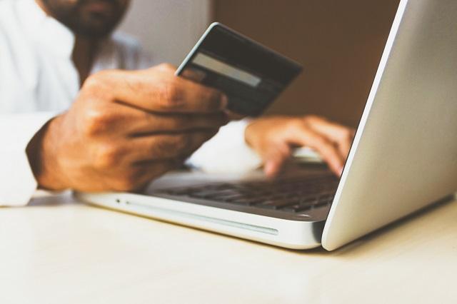 Mężczyzna przed koputerem z kartą kredytową