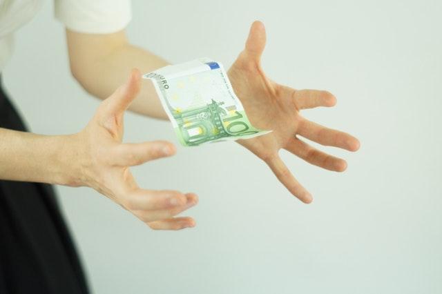 osoba łapie banknot